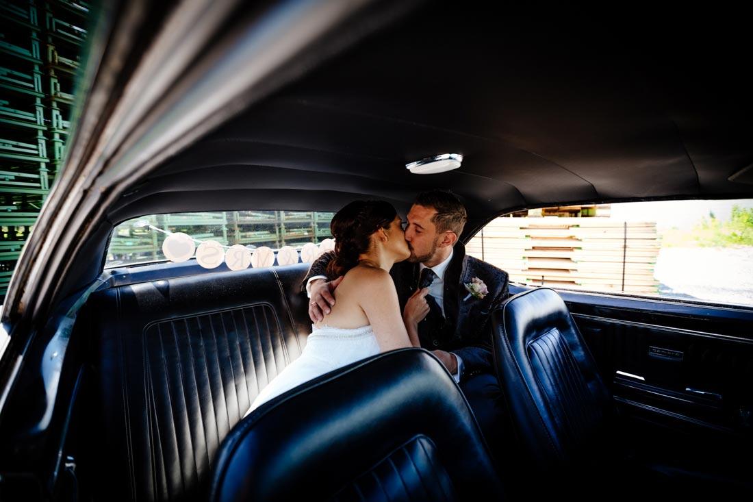 Hochzeitspaar küsst sich im Auto