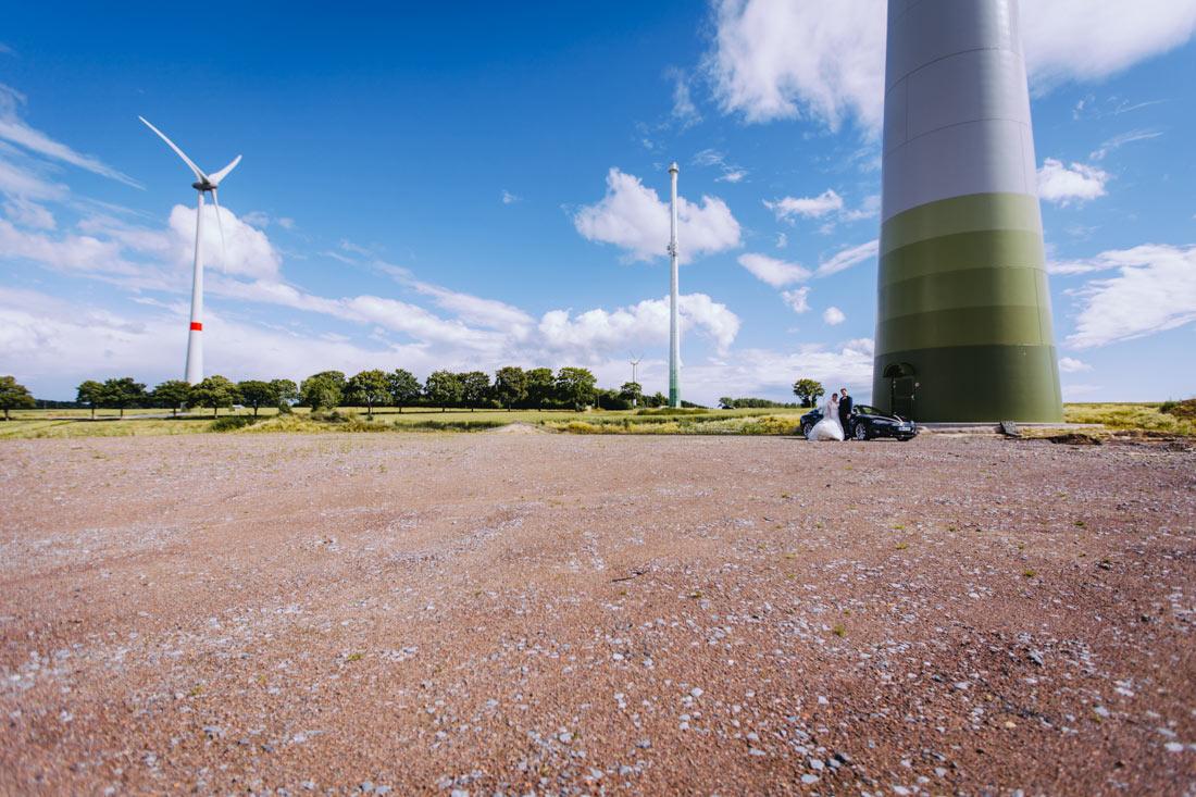 Brautpaar und Tesla vor Windkraftanlage