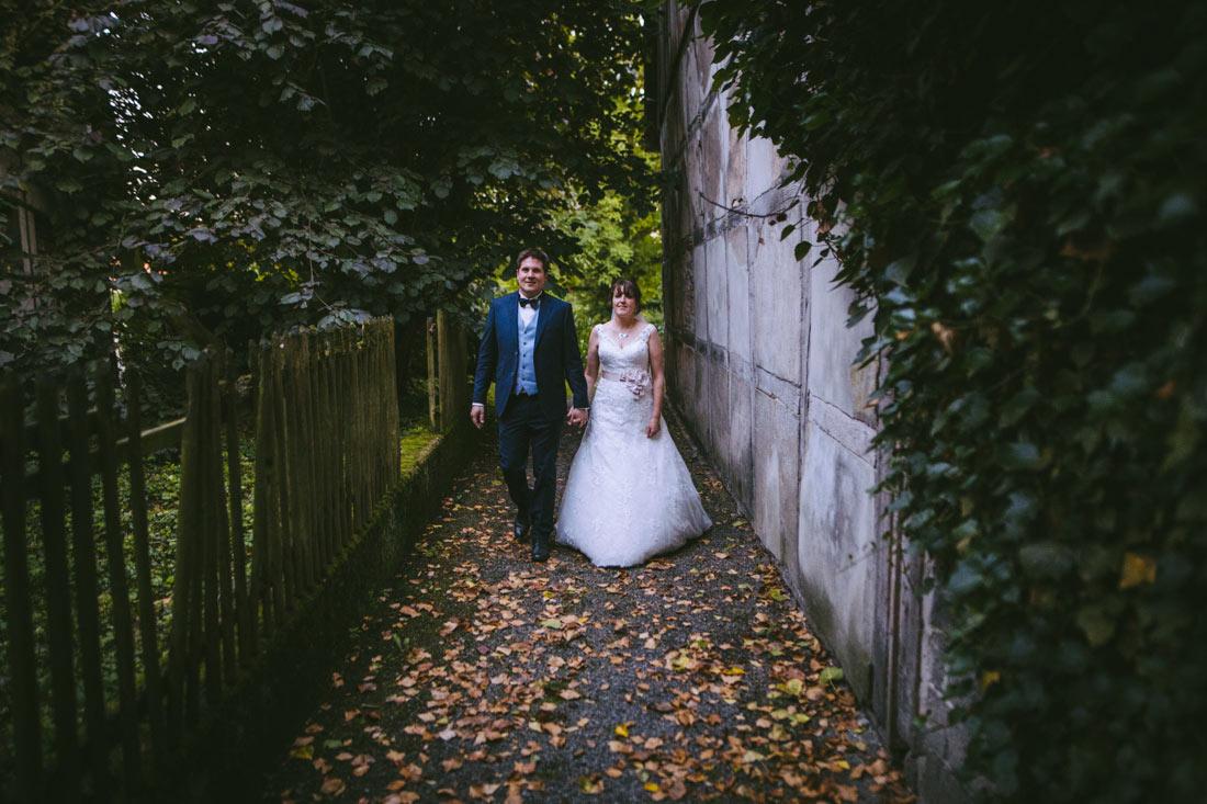 Hochzeitspaar läuft auf Laub