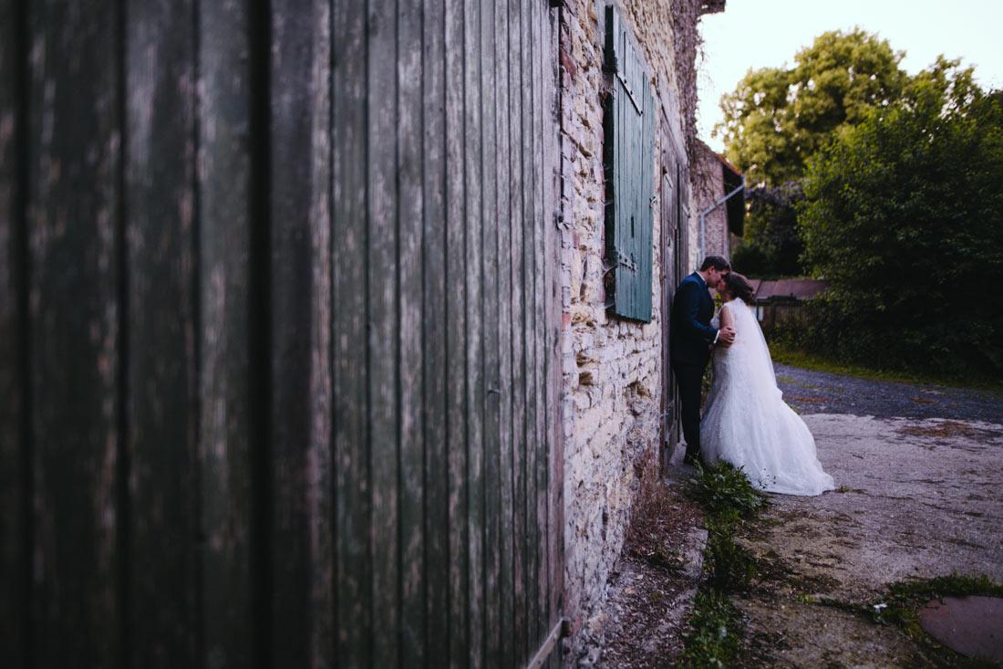 Hochzeitspaar küsst sich vor Scheune