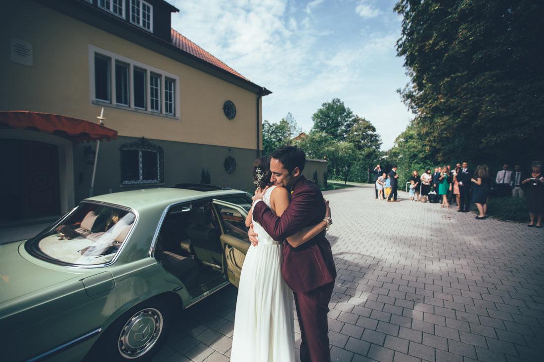 Brautpaar umarmt sich vor Hochzeitsauto