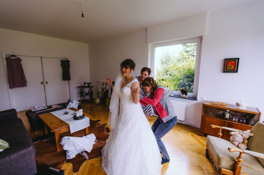 Braut bekommt das Kleid angezogen