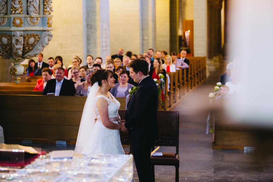 Brautpaar vor dem Altar sieht sich an