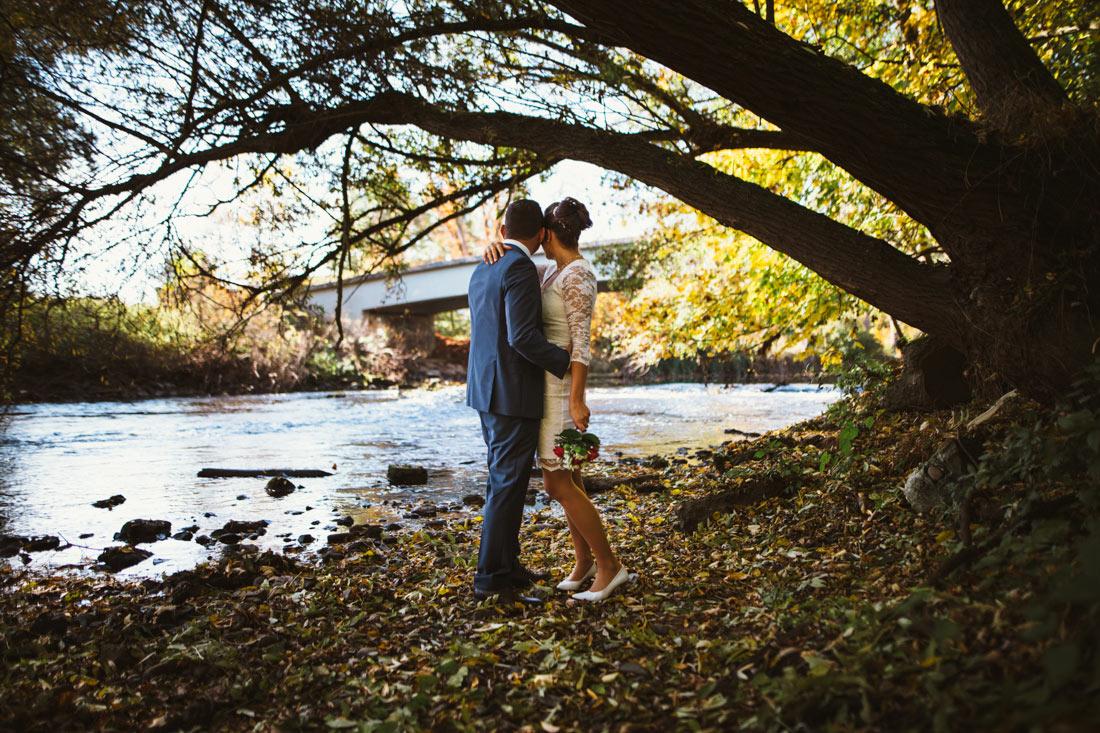 Hochzeitspaar steht am Fluss