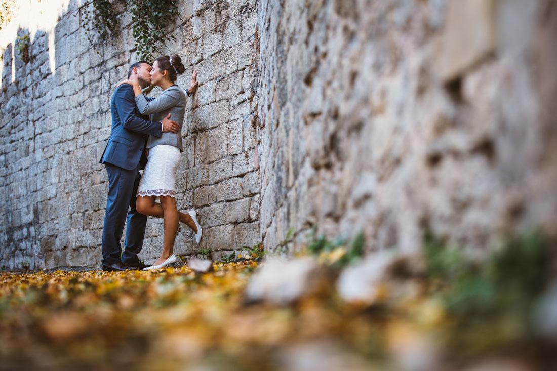 Hochzeitspaar küsst sich an einer Mauer