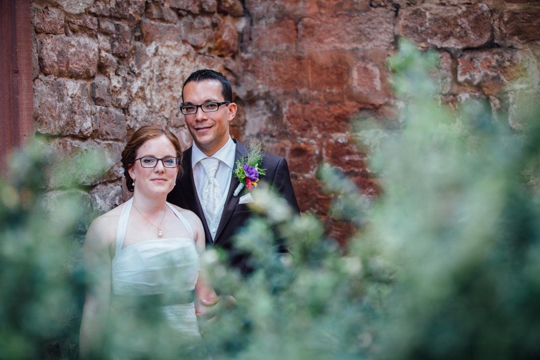 Das Brautpaar vor roter Mauer