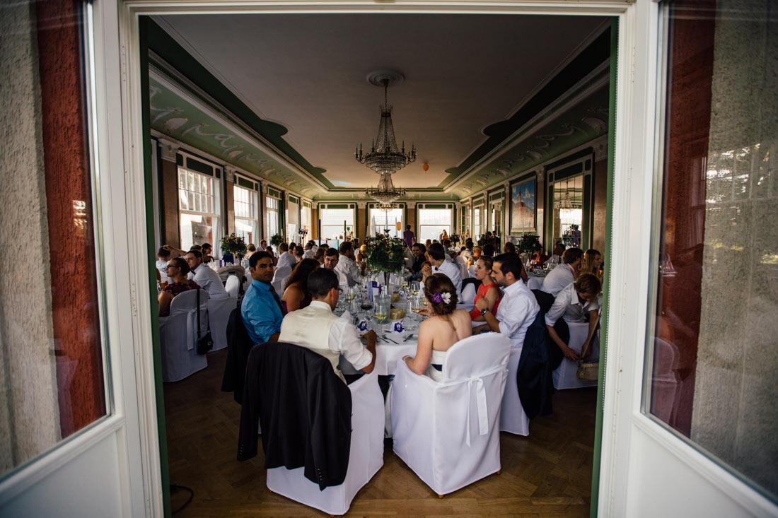 Hochzeitsgesellschaft nimmt im Saal Platz
