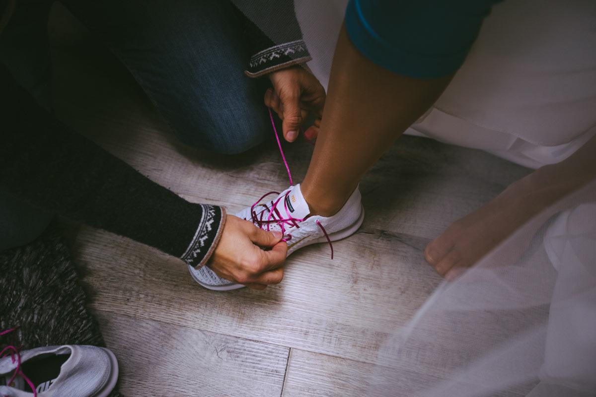 Braut bekommt die Schuhe gebunden