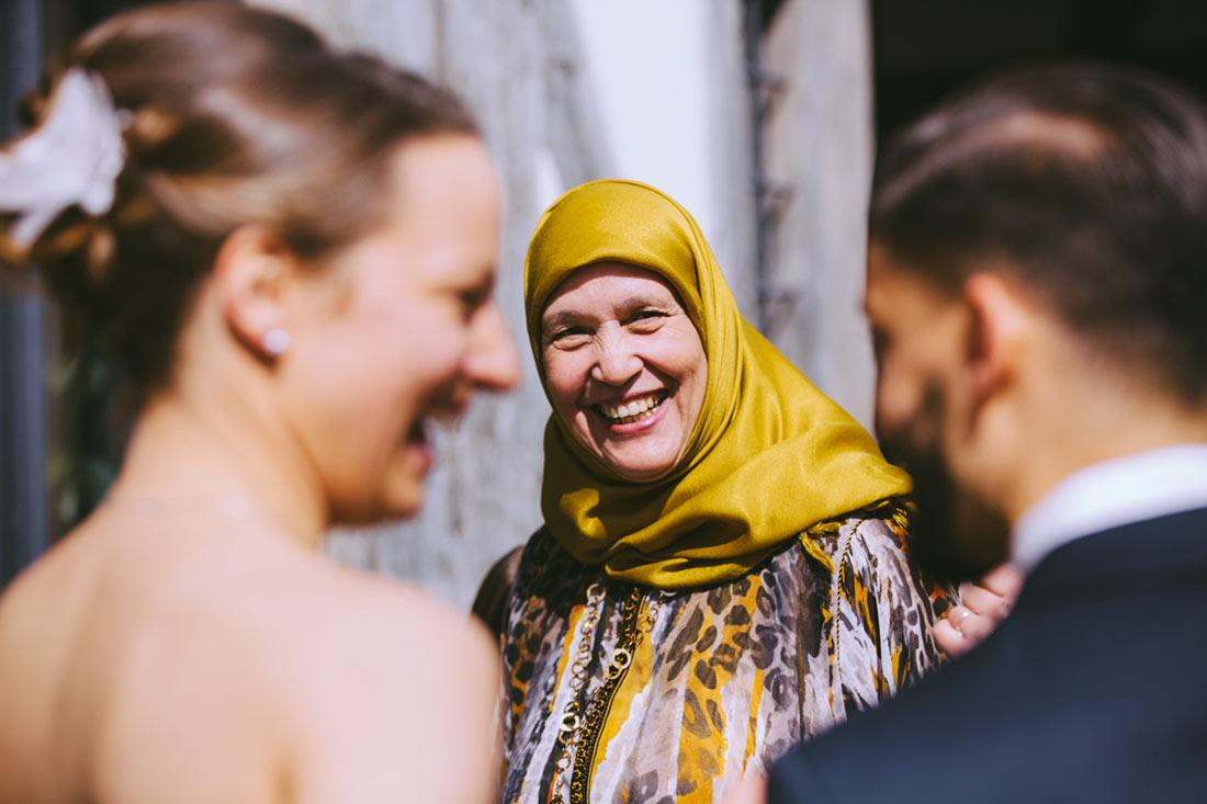 Frau lacht das Brautpaar an