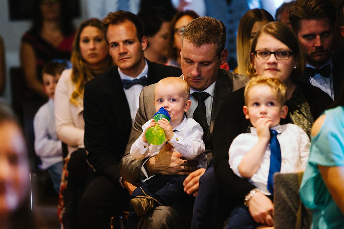 Kleines Kind mit Flasche im Publikum
