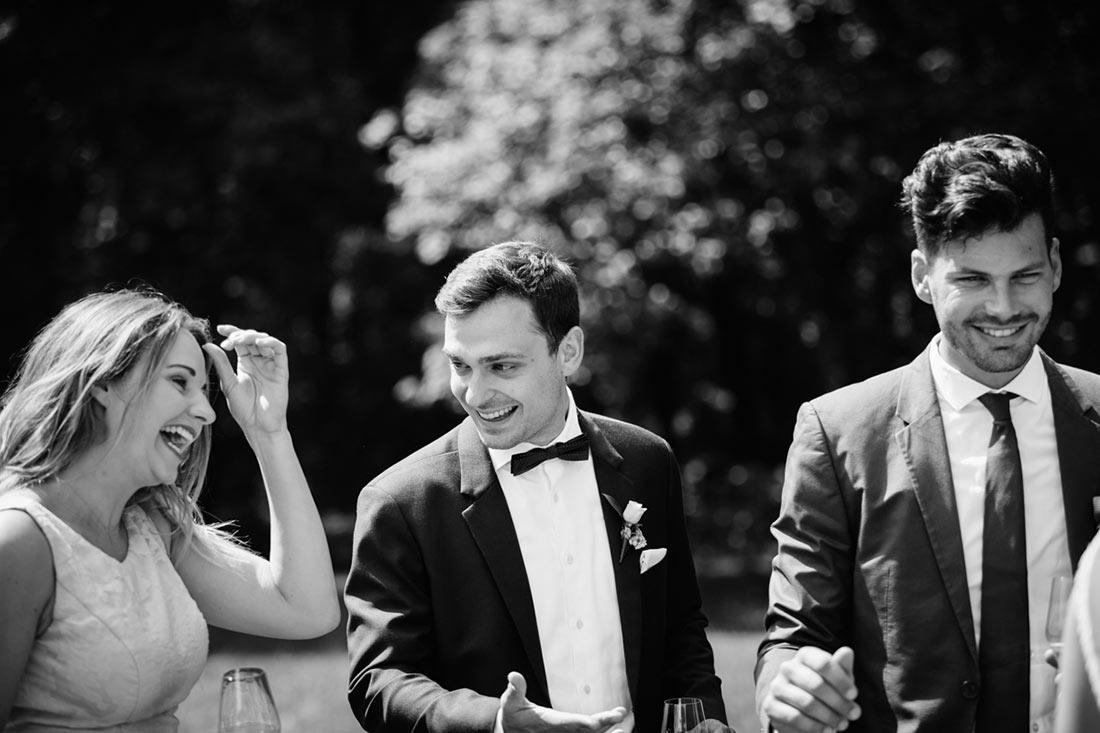 Lachende Gäste mit dem Bräutigam