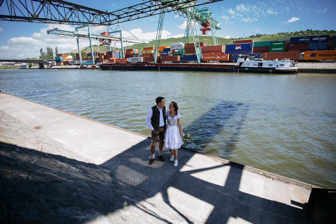 Hochzeitspaar steht am Neckar