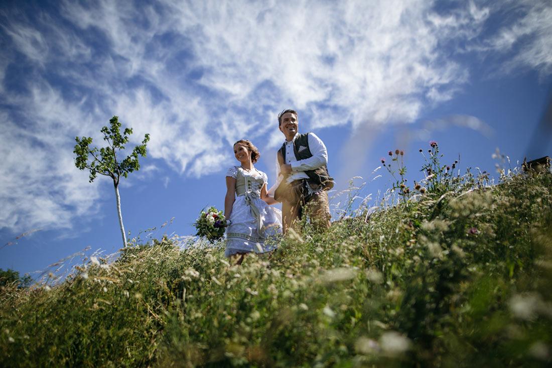 Lachendes Paar in Tracht in einer Wiese