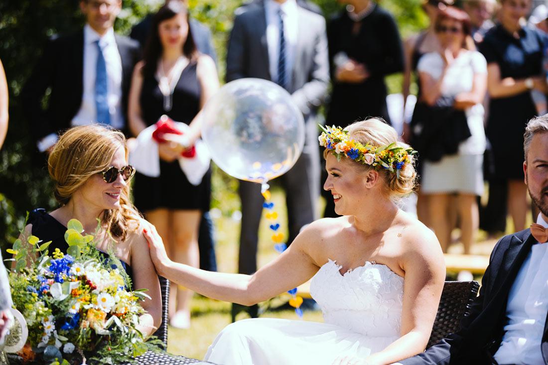 Braut und Trauzeugin lachen sich an