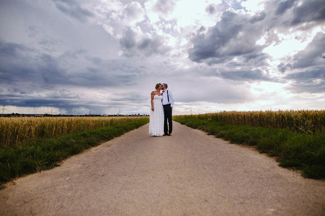 Brautpaar küsst sich auf Feldweg