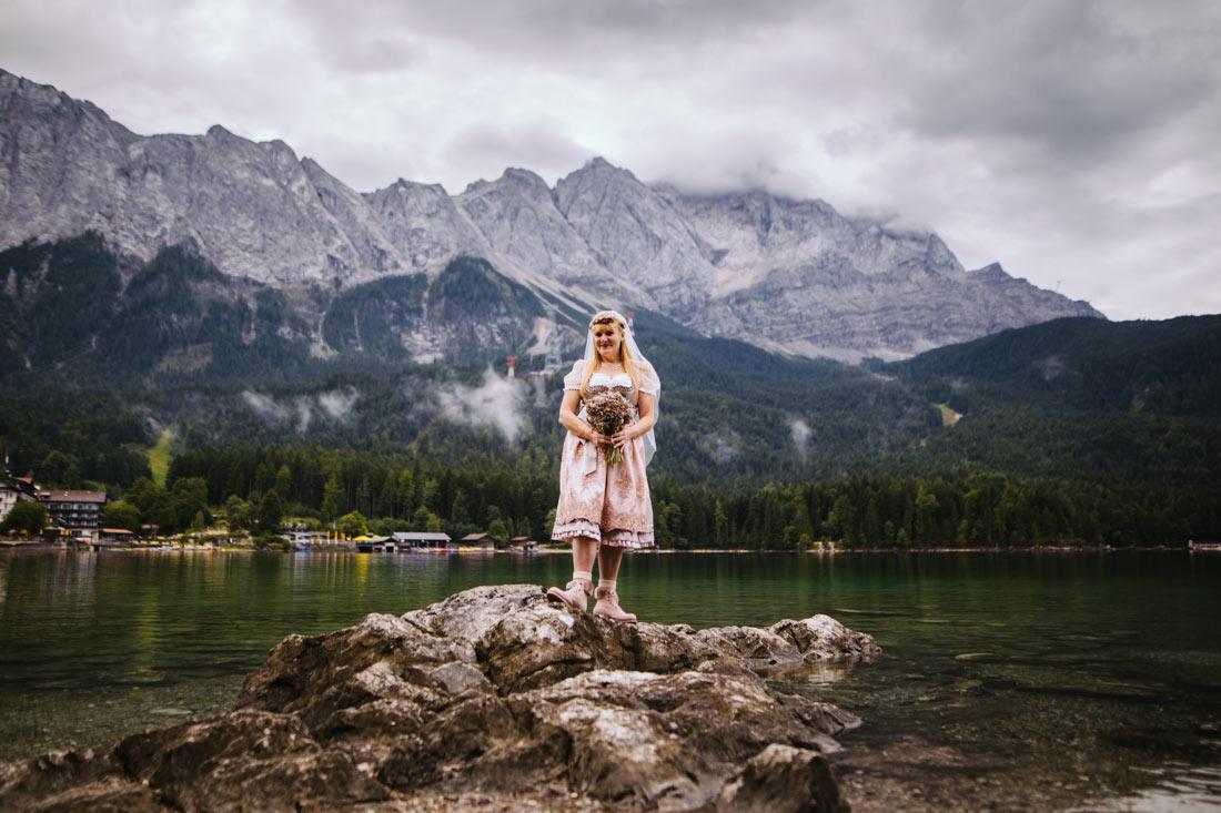 Die Braut steht im Dirndl vor dem Eibsee