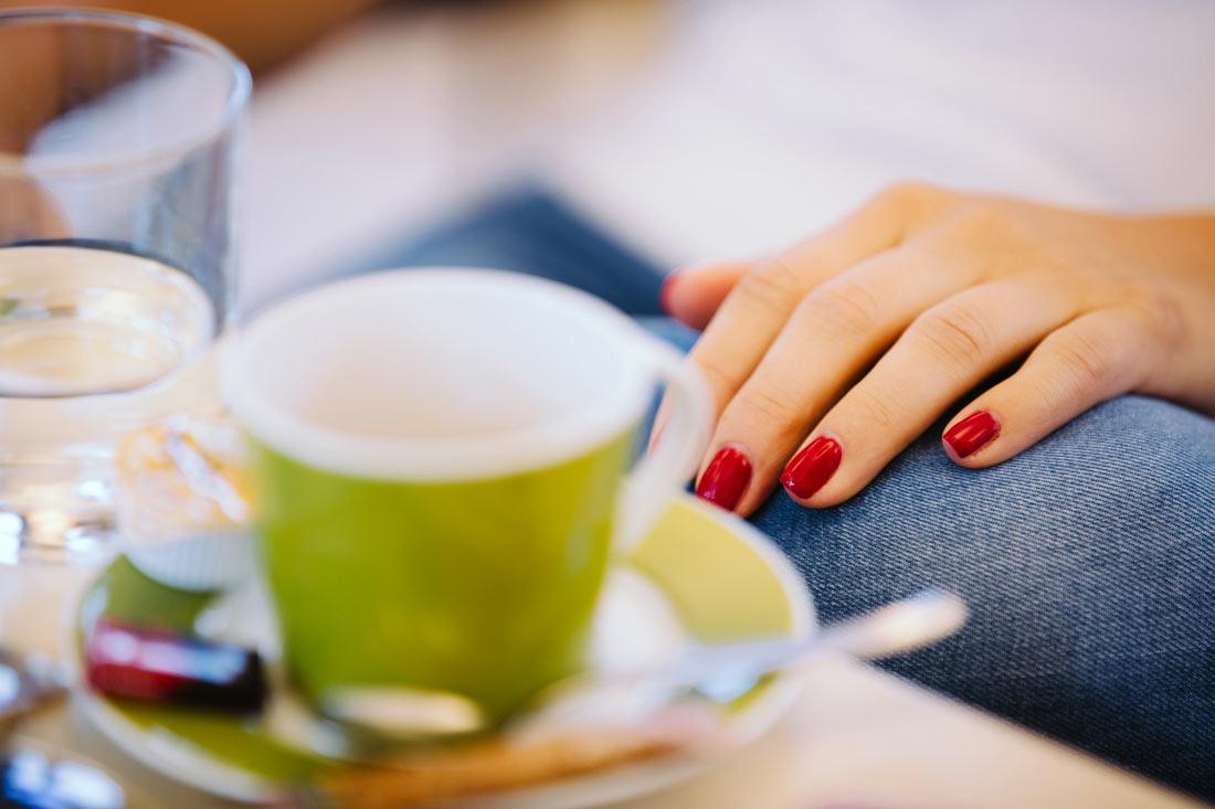 Kaffee und rote Fingernägel