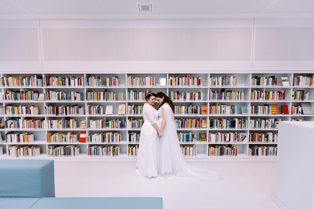 Hochzeitsppar steht vor Bücherregal