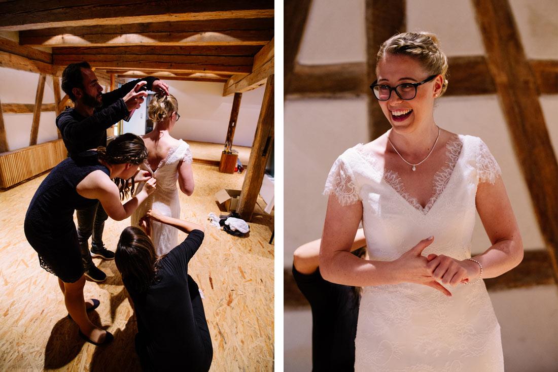 Die Braut bekommt das Kleid angezogen