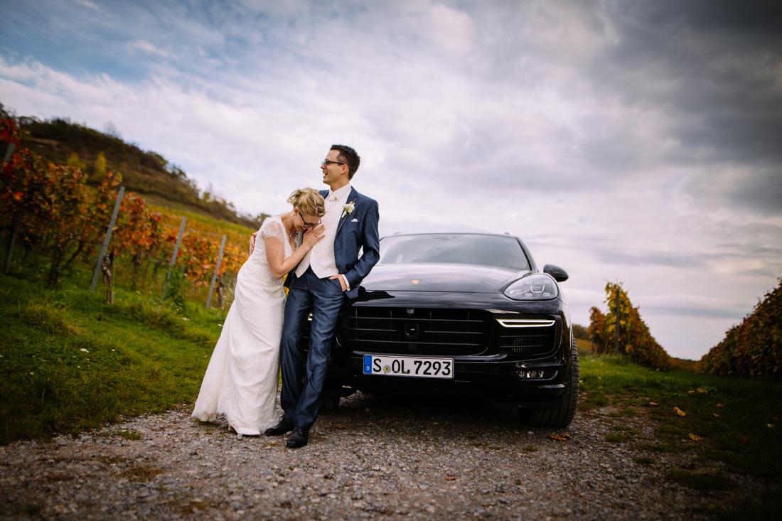 Paar lehnt am Hochzeitsauto