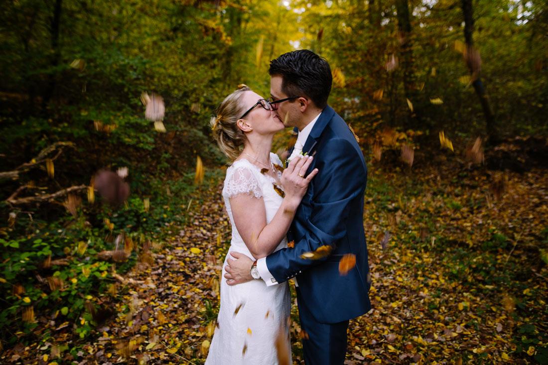 Braut küsst sich im Laub