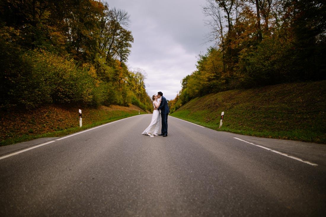 Hochzeitspaar küsst sich auf der Straße