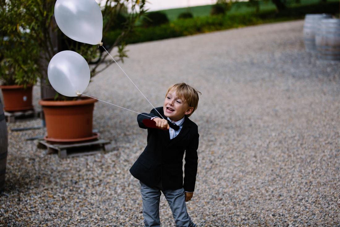 Kind spielt mit zwei Luftballons