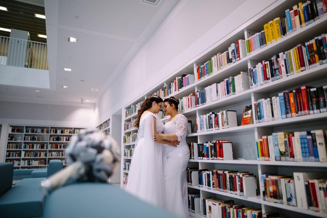 Paar lehnt sich am Bücherregal an