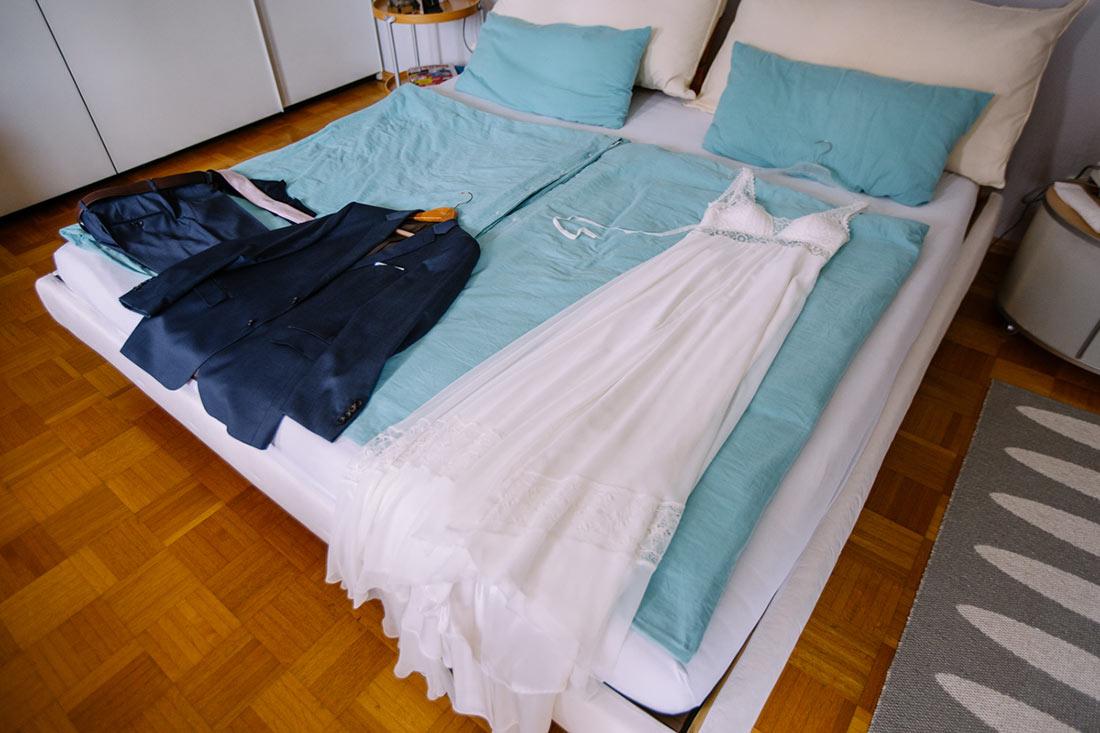 Hochzeitskleid und Anzug auf dem Bett