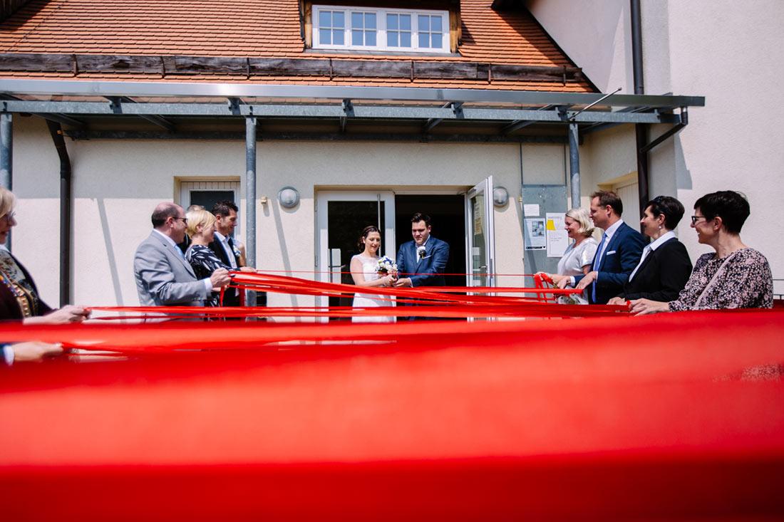 Hochzeitspaar schneidet sich dur rote Bänder
