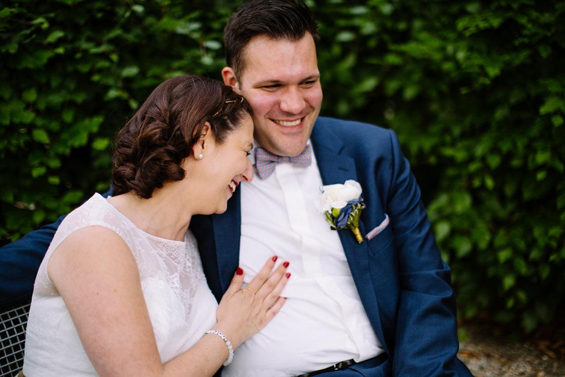 Hochzeitspaar lacht auf einer Parkbank