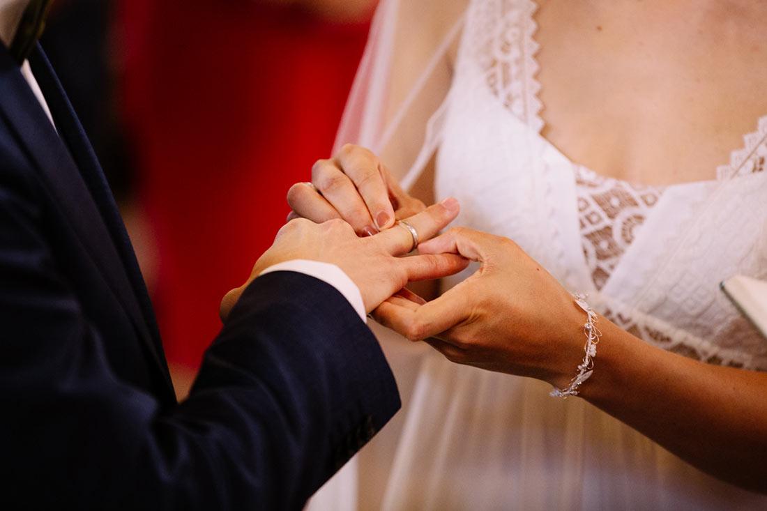 Braut steckt ihrem Mann den Ring an