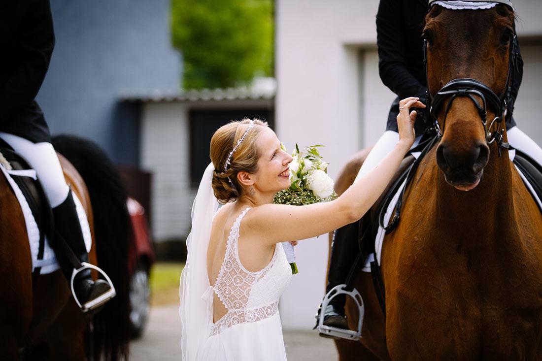 Die Braut streichelt ein Pferd