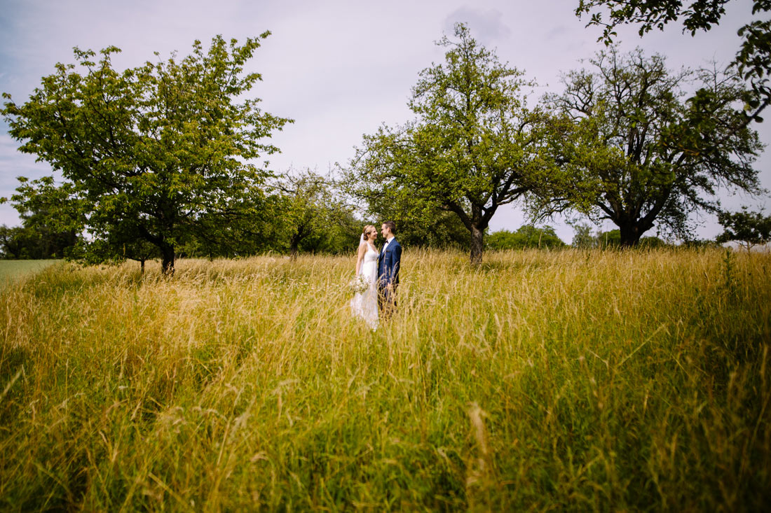 Hochzeitspaar steht in einer Wiese