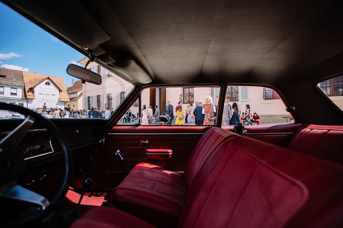 Blick auf die Gäste durch das Hochzeitsauto