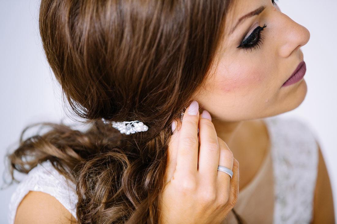 Braut bringt die Ohrringe an