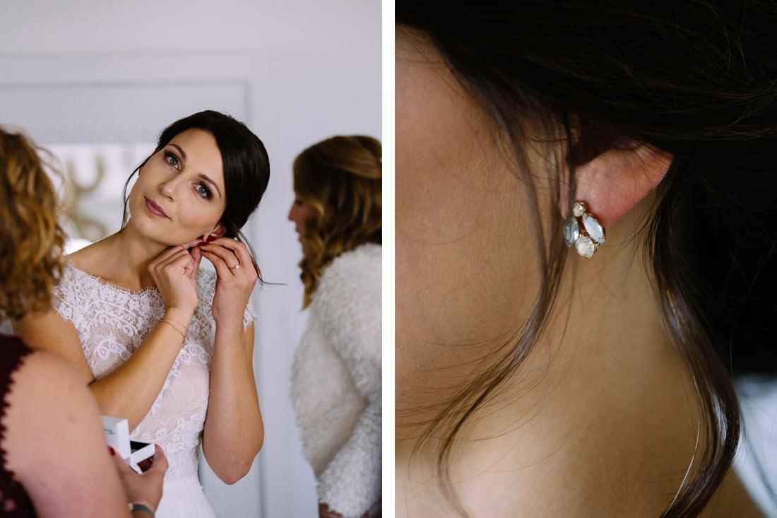 Braut steckt sich die Ohrringe an