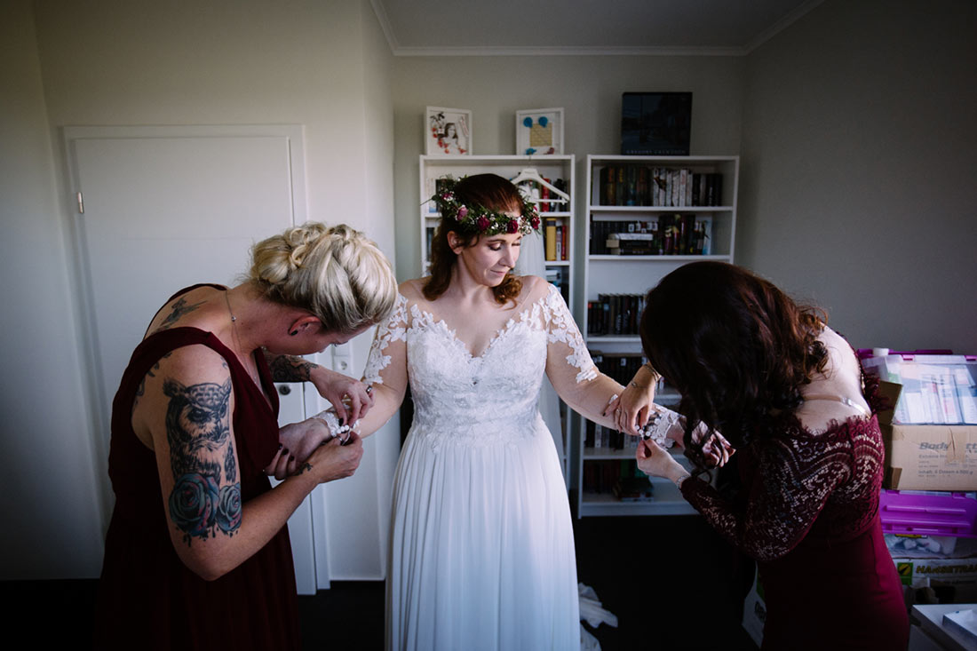 Braut zieht das Kleid an
